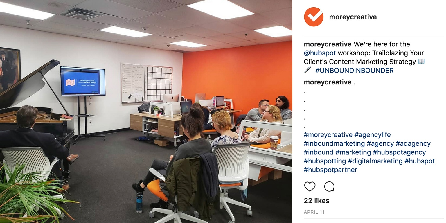 Screenshot of a photo from Morey Creative's Instagram showing the team watching a video on a tv